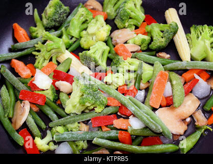Assortment of raw frozen vegetables in non stick skillet ready for cooking - Stock Photo