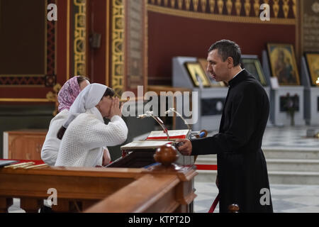 ROSTOV-ON-DON, RUSSIA - CIRCA NOVEMBER 2017: Orthodox priest talking with women inside a church - Stock Photo