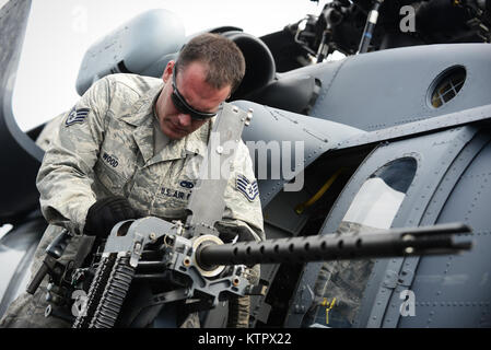 HOMESTEAD AIR RESERVE BASE, FL - Staff Sgt. Barry Wood, an airman with the 106th Rescue Wing, checks a .50 caliber - Stock Photo