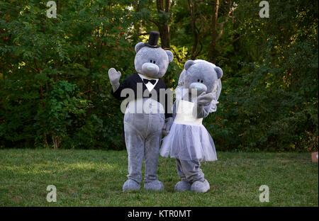 Couple dressed as teddy bear bride and groom standing in park - Stock Photo