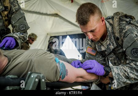 New York Army National Guard Pfc. Beau Fisher, assigned to Headquarters Co., 1st Battalion, 69th Infantry, administers - Stock Photo