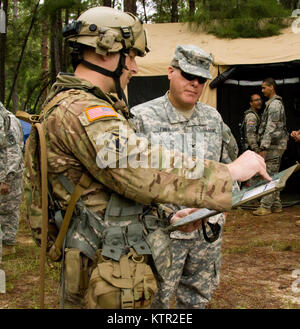 Massachusetts Army National Guard Col. Michael Finer, commander of the 79th Troop Command is briefed on a map by - Stock Photo