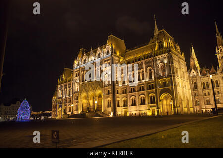 Budapest Parliament by night, Christmas 2017.  Large blue Christmas tree in Kossuth Ter with people gathering - Stock Photo