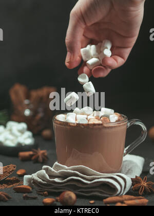 Marshmallows falls from hand in glass mug with hot chocolate cocoa drink. Copy space. Winter food and drink concept. - Stock Photo