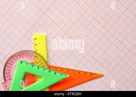 Various motley rulers lying on graph paper with copy space - Stock Photo