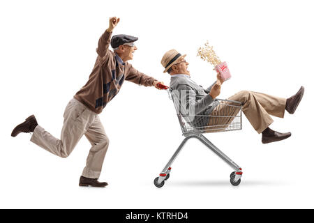 Senior with 3D glasses pushing a shopping cart with another senior with popcorn riding inside isolated on white - Stock Photo