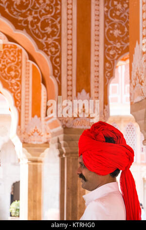 A guard in a red turban in the City Palace, Jaipur, Rajasthan,India - Stock Photo