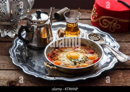 Fried egg with cured meat, traditional turkish breakfast, served in metal dishware, rustic - Stock Photo