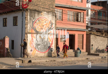People walk past wall mural in street scene, Kathmadu, Nepal - Stock Photo