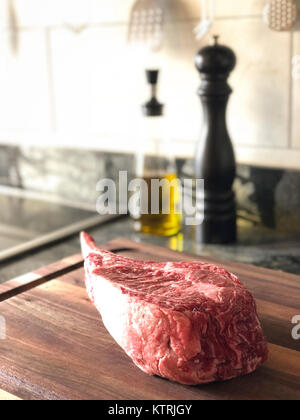 Close up of raw thick tomahawk ribeye beef steak on cutting board. Oil dispenser and pepper mill in the background. - Stock Photo