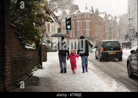 People walk through the snow during heavy snowfall on Muswell Hill Road in London, England on December 2017 - Stock Photo