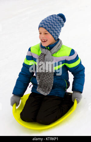 Small boy slides down a hill on a plate for driving on snow - Stock Photo