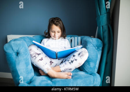 Funny happy toddler girl reading a book and playing in bed. Kids play at home. White nursery. Child in sunny bedroom. - Stock Photo