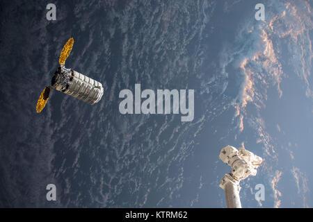 Orbital ATK's Cygnus resupply ship with its cymbal-ike UltraFlex solar arrays approaches the International Space - Stock Photo