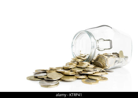 Overturned glass jar with golden and silver coins isolated on white background- Money saving financial concept