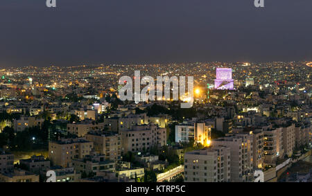View of Amman mountains and modern buildings at night - Stock Photo