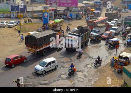 Traffic on damaged road with potholes in the city, Pune, Maharashtra - Stock Photo