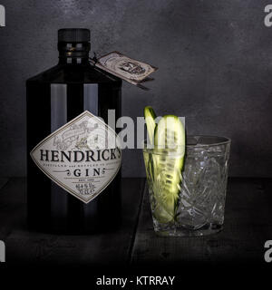 SWINDON, UK - DECEMBER 27, 2017: 70 cl bottle of Hendricks distilled gin with a glass and Cucumber on a Dark Rustic - Stock Photo