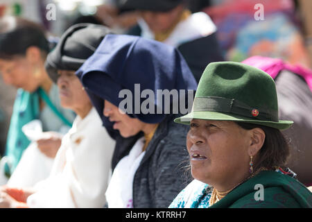 Otavalo, Ecuador-December 23, 2017: indigenous people sitting outdoors in the local market - Stock Photo