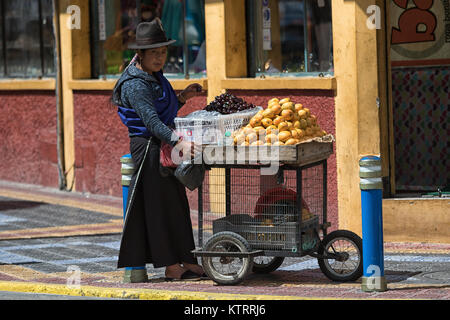 Otavalo, Ecuador-December 23, 2017: indigenous woman selling fruits om the street n the popular tourist town - Stock Photo