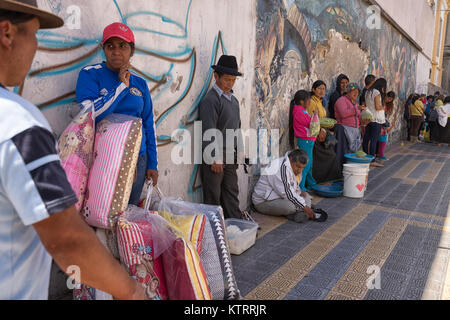 Otavalo, Ecuador-December 23, 2017:people cooling down in the shade on a hot day - Stock Photo