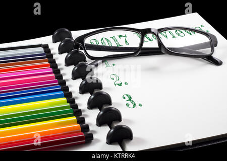 2017 Reviews text on white sketchbook with color pen and eye glasses - Stock Photo