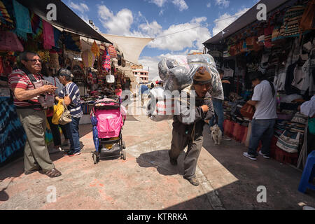 Otavalo, Ecuador-December 23, 2017: local man hauling merchandise through the artisan market on his back - Stock Photo