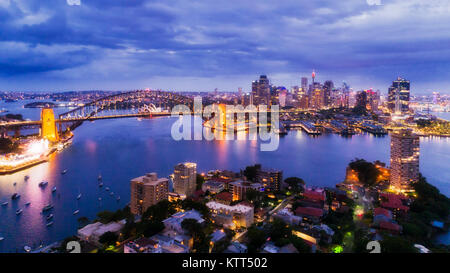 Sydney city CBD from Blues Point and North Sydney at sunset with bright illiumination of famours landmarks around - Stock Photo