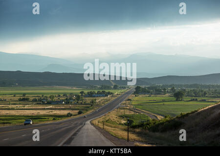 Straight road leading to mountains, Wyoming, United States - Stock Photo