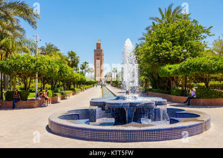 Marrakesh, Morocco - May 12, 2017: People are sitting and relaxing next to the fountain in the Koutoubia Gardens - Stock Photo