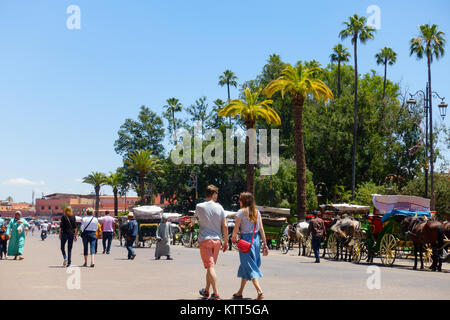 Marrakech, Morocco - May 12, 2017: Tourists and locals are walking on the street leading towards the famous Jemaa - Stock Photo