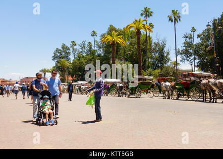 Marrakech, Morocco - May 12, 2017: Moroccan man selling merchandise to tourists on the street leading towards Jemaa - Stock Photo