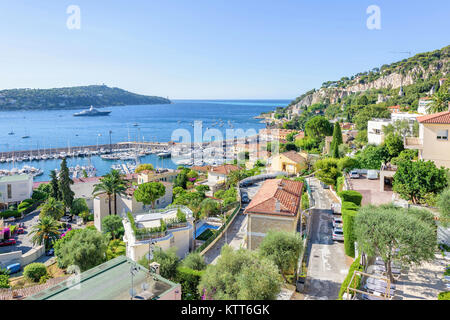 Daylight view to city buildings, port and yachts cruising on water. Blue sky and ocean. Green mountains with trees, - Stock Photo