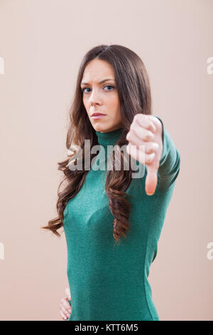 Portrait of displeased women who is showing thumb down - Stock Photo