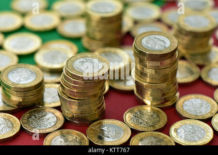 a large number of one pound coins on a red and green background in piles of cash. A lot of money in cash stacks - Stock Photo