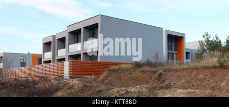 Panorama of a modern standard no name  unfinished houses on wet clay hill. Mass production.  Panoramic collage from - Stock Photo