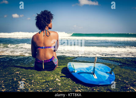 Surfer girl with afro hairstyle sitting next to blue surfboard on the green coral reef in front of a breathtaking - Stock Photo