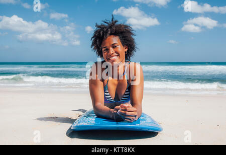 Surfer girl with afro hairstyle smiling, lying down on blue surfboard on the white sand at Dreamland beach, Bali, - Stock Photo