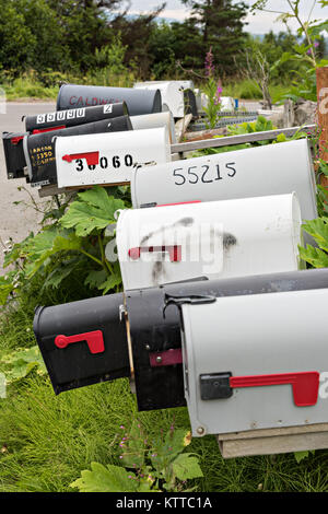 Rural mailboxes line a street corner in remote Fritz Creek, Alaska. - Stock Photo