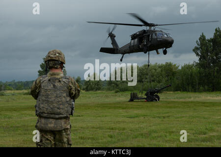 A U.S. Army Soldier assigned to Bravo Battery 2nd Battalion, 15th Field Artillery Regiment, 2nd Brigade Combat Team, takes a picture of a UH-60 Black Hawk Helicopter lifting a M119A2 Howitzer on Fort Drum, N.Y., July 14, 2017. Soldiers from Bravo Battery were conducting air artillery raids. (U.S. Army National Guard photo by Pfc. Andrew Valenza)