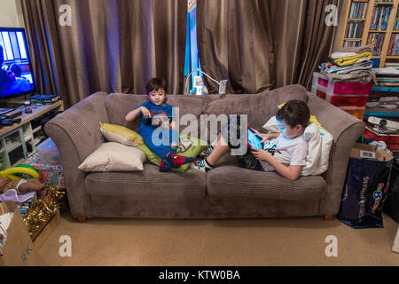 Two young brothers sit together on a sofa in the living room and play on their tablets in an evening. - Stock Photo