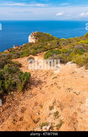 ZAKYNTHOS, GREECE, 27 September, 2017: Tourists walk on cliff near Shipwreck (Navagio) beach, panoramic scenic view - Stock Photo