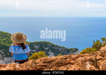 ZAKYNTHOS, GREECE, 27 September, 2017: Woman admiring the Shipwreck (Navagio) Beach, from the cliff. Zakynthos Island - Stock Photo