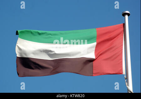 the flag of the United Arab Emirates against blue sky - Stock Photo