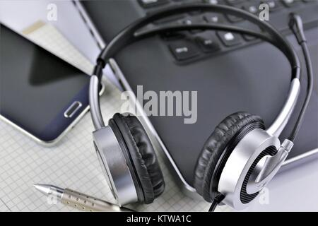 An concept Image of a Office desk with a Headset and a Keyboard - Stock Photo