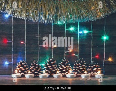Festive new year and Christmas concept. Colorful lights of garlands, fir cones and candles on the background of - Stock Photo