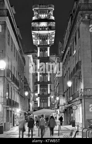 People in nocturnal downtown Lisbon with illuminated Santa Justa elevator in the center - Stock Photo