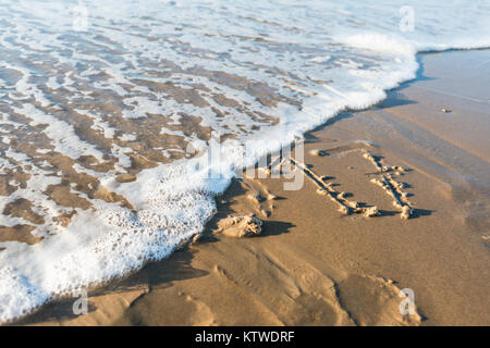 year 2017 written in the sand of the beach - Stock Photo
