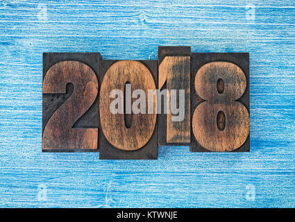 Year 2018 set with vintage letterpress printing blocks on blue painted wood - Stock Photo
