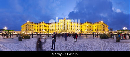 Panormaic view of illuminated Schönbrunn palace in Christmas time with fairy lights decorated Christmas tree and - Stock Photo